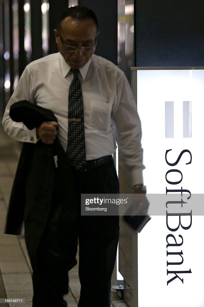 A man walks past a sign bearing the Softbank Corp. logo outside the company's store in Tokyo, Japan, on Monday, Oct. 15, 2012. Softbank agreed to pay $20.1 billion to acquire about a 70 percent stake in Sprint Nextel Corp. as Japan's third-biggest mobile-phone operator seeks growth overseas amid a declining local market. Photographer: Kiyoshi Ota/Bloomberg via Getty Images
