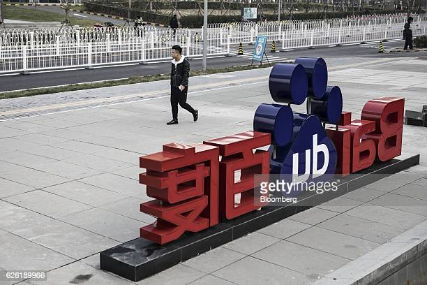 A man walks past a sign for Baidu Inc at the entrance to the Baidu Technology Park in Beijing China on Friday Nov 25 2016 Baidu serves 6 billion...