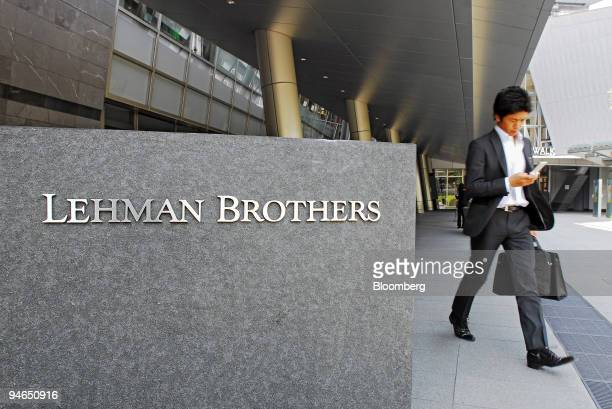 Man walks past a sign for Lehman Brothers Inc. In the Roppongi Hills district of central Tokyo, Japan, on Thursday, May 24, 2007. Lehman Brothers...