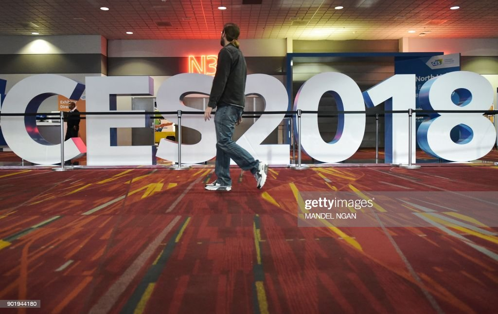 A man walks past a sign for the 2018 Consumer Electronics Show at the Las Vegas Convention Center in Las Vegas on January 6, 2017. The 2018 CES runs from January 9-12. /