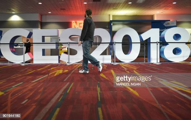 A man walks past a sign for the 2018 Consumer Electronics Show at the Las Vegas Convention Center in Las Vegas on January 6 2017 The 2018 CES runs...