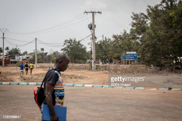 Man walks past a sign for the Republic of Guinea, which marks the border with Sierra Leone. The latest Ebola outbreak in Guinea was declared in...