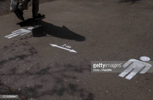 A man walks past a sign on the pavement indicating social distancing measures in Ruskin Park on April 16 2020 in London UK The Coronavirus pandemic...