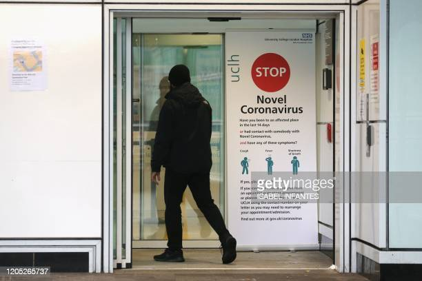 A man walks past a sign providing guidance information about novel coronavirus at one of the entrances to University College Hospital in London on...