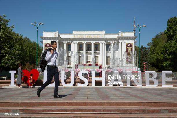A man walks past a sign reading 'I Love Dushanbe' in front of the Ayni Opera and Ballet Theater in Dushanbe Tajikistan on Saturday April 21 2018...