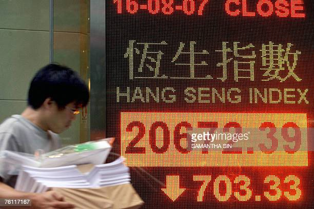 A man walks past a sign showing the closing numbers of Hong Kong's Hang Seng Index 16 August 2007 Hong Kong share prices closed sharply lower down 33...
