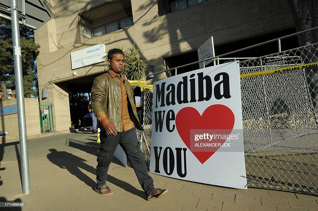 A man walks past a sign wishing well former South African president Nelson Mandela on June 25, 2013 outside of the Mediclinic heart hospital in Pretoria where Mandela is receiving treatment. Mandela's close family gathered today at his rural homestead to discuss the failing health of the South African anti-apartheid icon who was fighting for his life in hospital. Messages of support poured in from around the world for the Nobel Peace Prize winner, who spent 27 years behind bars for his struggle under white minority rule and went on to become South Africa's first black president.