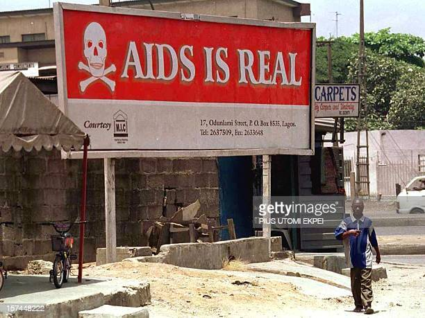 A man walks past a signboard warning residents that the threat of HIV/AIDS is real 31 March 2001 in Lagos Nigeria While surveys show sex among the...