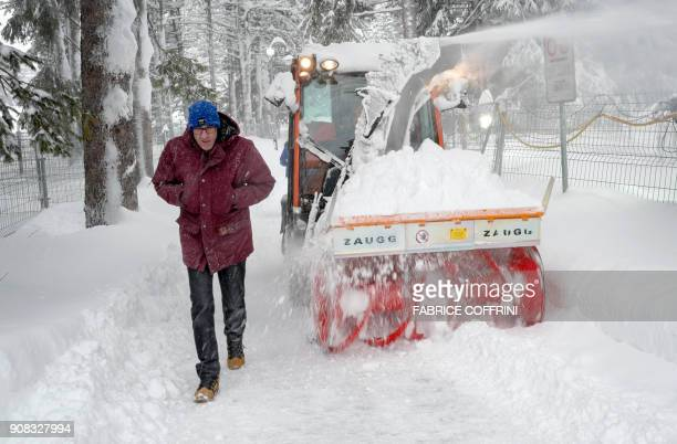 A man walks past a snow blower clearing a path close to the Davos Congress Centre ahead of the opening of the World Economic Forum 2018 annual...