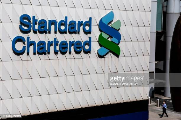 A man walks past a Standard Chartered bank in Hong Kong on February 27 2020 Standard Chartered said that its pretax profit rose to 42 billion USD in...