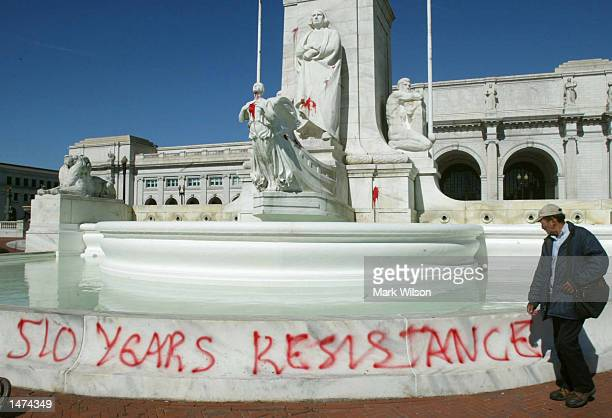 A man walks past a statue of Christopher Columbus that was vandalized with red paint at Union Station October 14 2002 in Washington DC The fountain...