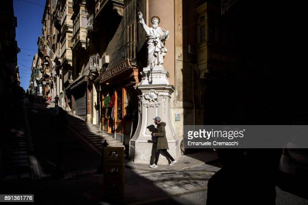 A man walks past a statue of Saint Paul in Trik San Pawl on December 7 2017 in Valletta Malta Valletta a fortified town that dates back to the 16th...