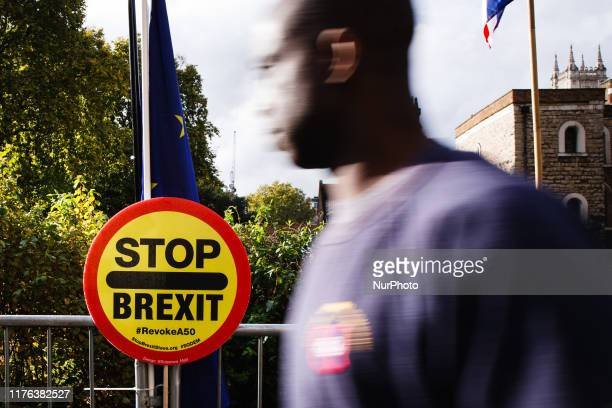 A man walks past a 'Stop Brexit' placard fixed to railings on Abingdon Street outside the Houses of Parliament in London England on October 17 2019...