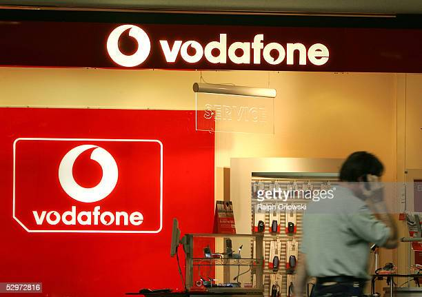 A man walks past a store of British mobile telephone giant Vodafone at the company's offices May 24 2005 in Duesseldorf Germany Vodaphone announced a...