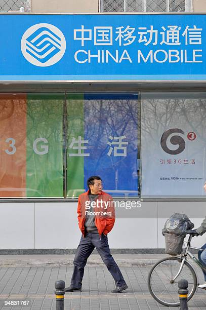 A man walks past a store offering China Mobile Ltd services in Beijing China on Wednesday Jan 7 2009 China will issue licenses for highspeed...