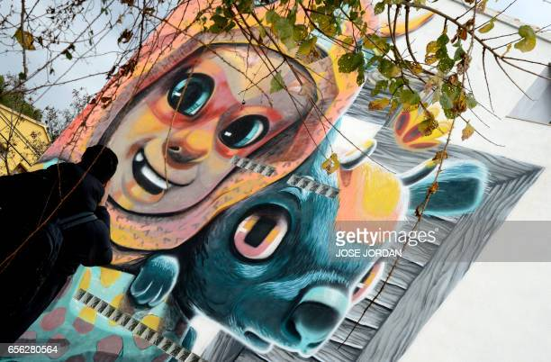 A man walks past a street art mural on the facade of a house in Fanzara near Castellon de la Plana on December 15 2016 Fanzara a Spanish hamlet in...