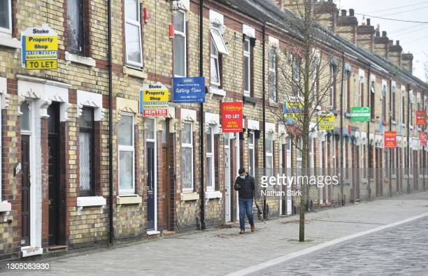 Man walks past a street of terraced houses advertising properties To Let on March 03, 2021 in Stoke-on-Trent, England. UK Chancellor, Rishi Sunak,...