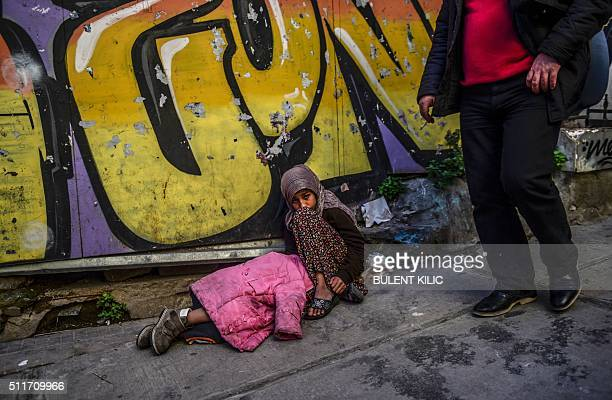A man walks past a Syrian girl who begs in the street as another child sleeps next to her in downtown Istanbul on February 22 2016 / AFP / BULENT...