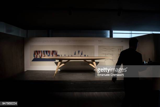 A man walks past a table designed by Gio Ponti at the Molteni C display stand during the Salone Internazionale del Mobile at Fiera di Rho on April 17...