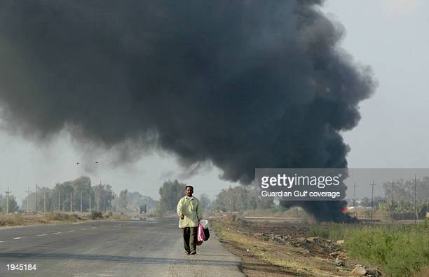 Man walks past a tank exploded by U.S. Forces April 17, 2003 in Baghdad, Iraq. Part of clean up efforts for U.S. Troops includes the detonation of...