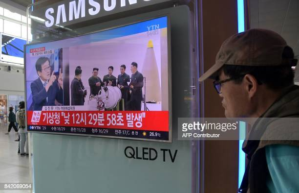 A man walks past a television display at a train station in Seoul on September 3 2017 showing a news broadcast about North Korea's latest possible...