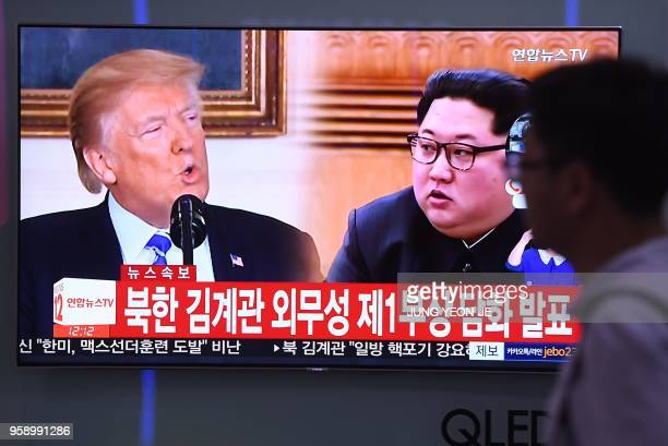 A man walks past a television news screen showing North Korean leader Kim Jong Un and US President Donald Trump at a railway station in Seoul on May...