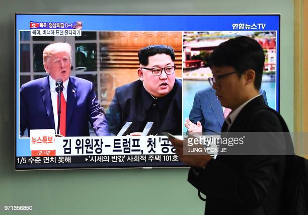 A man walks past a television news screen showing US President Donald Trump and North Korean leader Kim Jong Un at a train station in Seoul on June...