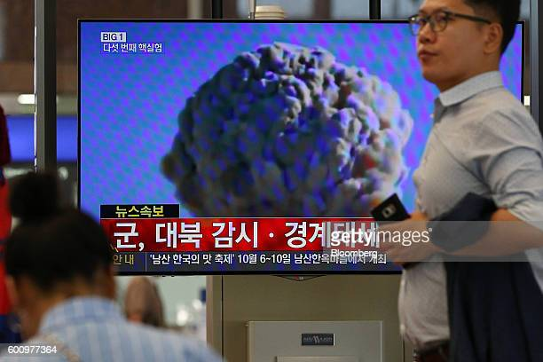 A man walks past a television screen showing a news broadcast on North Korea's nuclear test at Gimhae International Airport in Busan South Korea on...
