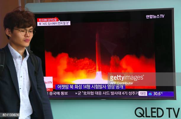 A man walks past a television screen showing a video footage of North Korean leader Kim JongUn celebrating his country's latest test launch of an...
