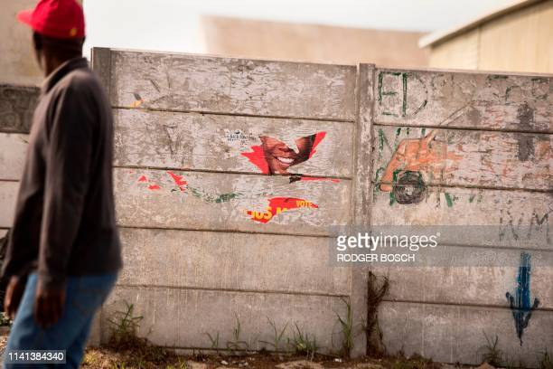A man walks past a torned political poster of the South African opposition and far left party Economic Freedom Fighters picturing the face of their...