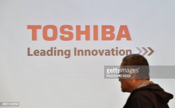 A man walks past a Toshiba logo prior to a news conference at the company's headquarters in Tokyo on March 14 2017 The troubles at crisishit Toshiba...