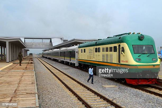 A man walks past a train of the newly completed AbujaKaduna night railway line in Abuja on July 21 2016 Nigerias first high speed rails system which...