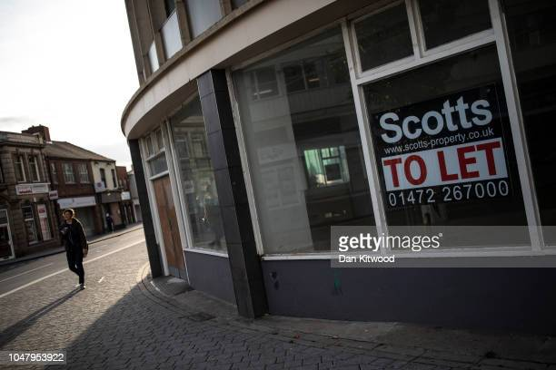 A man walks past a vacant high street shop on October 8 2018 in Grimsby England Grimsby was once home to the largest fleet of fishing trawlers in the...