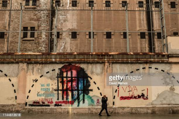 Man walks past a vandalized mural of Jordi Cuixart, leader of Omnium Cultural, who has been in jail since October 2017 awaiting trial for his role in...