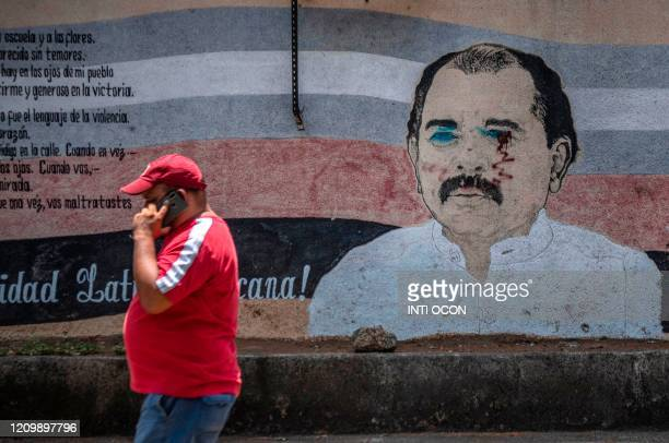 A man walks past a vandalized mural of Nicaragua's President Daniel Ortega in Managua on April 14 2020 during the pandemic of the novel coronavirus...