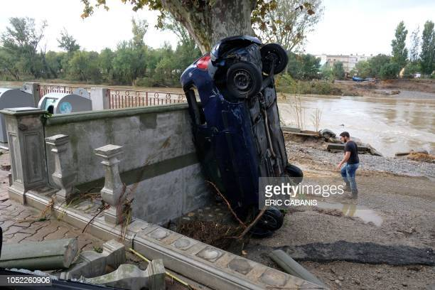 Man walks past a vehicle swept away on the bank of the Aude river, in Trebes, near Carcassonne, southern France on October 16, 2018 after the floods....
