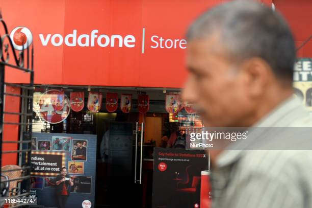 Man walks past a Vodafone store in Kolkata, India, 29 November, 2019. India's telecom service providers seek aid from the government for running...