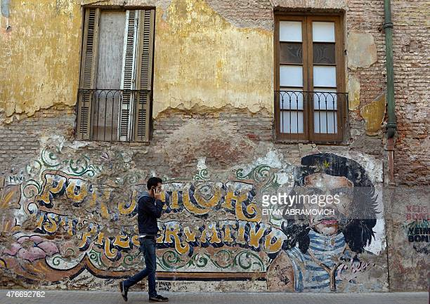 A man walks past a wall decorated with the image of Argentineborn revolutionary Ernesto Che Guevara in downtown Buenos Aires Argentina on June 11...