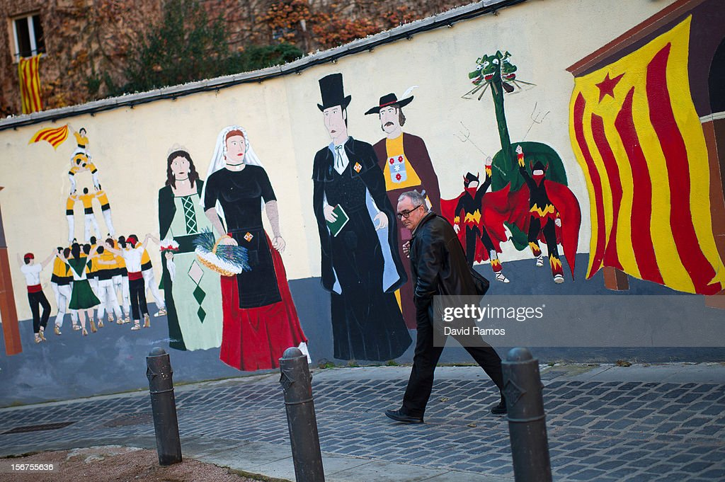 A man walks past a wall painted with a pro-independent Catalonia flag, known as 'Estelada,' and traditional Catalan figures on November 20, 2012 in Vic, Spain. Catalans will be voting in Parliamentary elections on November 25.