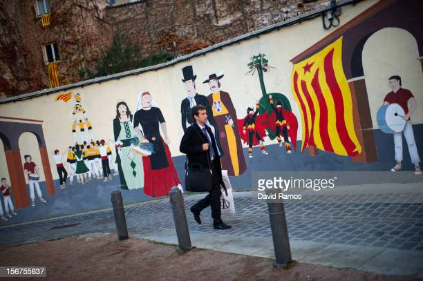 A man walks past a wall painted with a proindependent Catalonia flag known as 'Estelada' and traditional Catalan figures on November 20 2012 in Vic...
