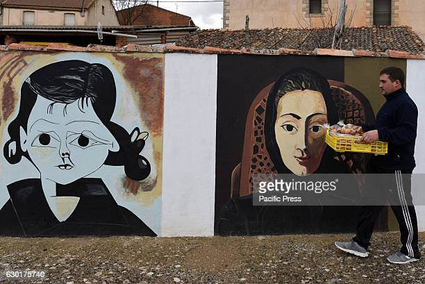A man walks past a wall painted with replicas of works by Spanish genius Pablo Picasso