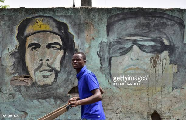 A man walks past a wall with portraits of Argentineborn guerrilla leader Ernesto 'Che' Guevara and former Libyan dictator Muammar Gaddafi in a...