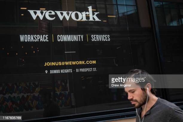 Man walks past a WeWork office facility in the DUMBO neighborhood in the Brooklyn borough of New York City on September 13, 2019. WeWork has chosen...
