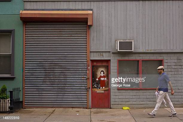A man walks past a Williamsburg apartment on May 5 2012 in New York City Over the past five years Williamsburg has become a magnet for youthful...