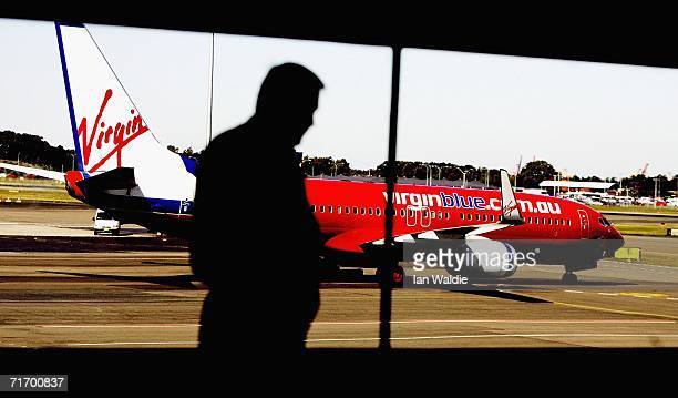 A man walks past a window as a Virgin Blue aircraft taxis at Sydney's Mascot airport August 23 2006 in Sydney Australia Virgin Blue today announced...
