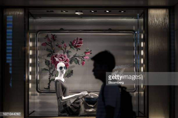 A man walks past a window display of a Fendi SpA store at night in the Ginza area of Tokyo Japan on Tuesday Aug 21 2018 Japan is scheduled to release...
