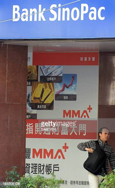 A man walks past advertising of the Bank of SinoPac in Taipei on April 3 2013 Share prices on Taiwan's SinoPac Financial Holdings rose 28 percent...