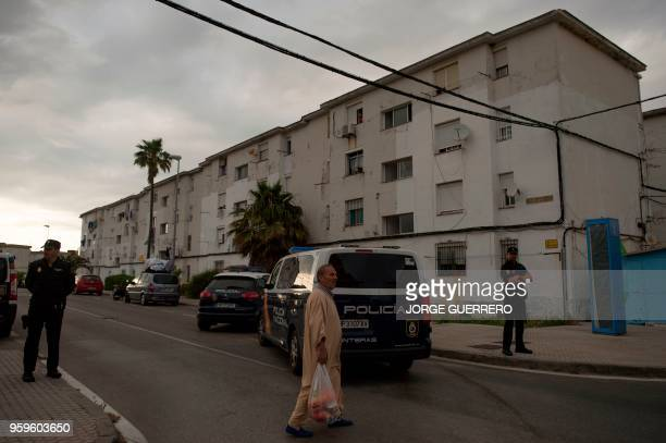 A man walks past agents of the Police Intervention Unit standing guard in the neighborhood of La Pinera in Algeciras on May 17 2018 Three people have...
