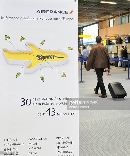 A man walks past an advert marking the kickoff of Air France's new organization in the French regions at French airline Air France first regional...
