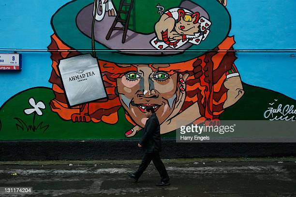 A man walks past an advertisement for Ahmad Tea painted on the side of an apartment block on November 2 2011 in Yekaterinburg Russia Yekaterinburg is...